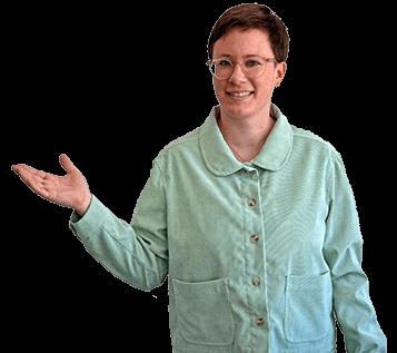 Halbkörper-Portrait von Maya. Maya ist eine nichtbinäre, weisse Person mit kurzen braunen Haaren und einer Brille. Maya trägt einen lindgründen Blazer und streckt die rechte Hand zur Seite.